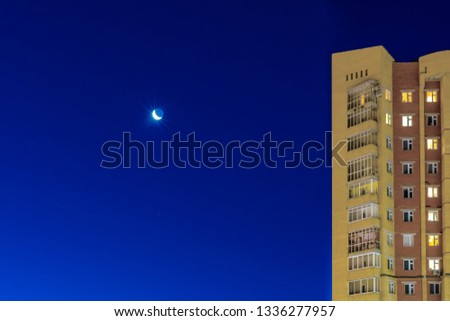 The month is shining, the month is shining and the stars are against a blue bright sky, against the background of a residential building. Template for design. #1336277957