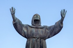 The monument to St. Francis of Assisi (1182-1226), in Rome, Italy. Bronze statue on a light blue background.