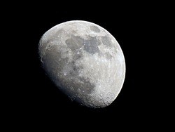 The moon at Waxing gibbous phase. Focus on lunar rugged surface of craters and geological features. Detail of Copernicus and Tycho large impact craters clearly defined on terrain
