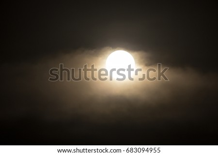 The moon in the haze of the clouds at night #683094955