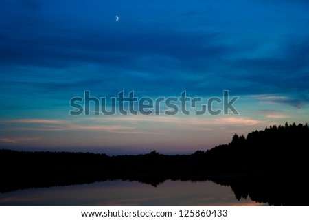 the moon in the late evening sky over the lake