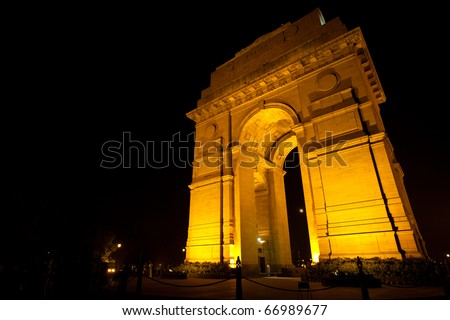 The moon is faintly visible through India Gate memorial, tastefully lighted by floodlights at night in Delhi