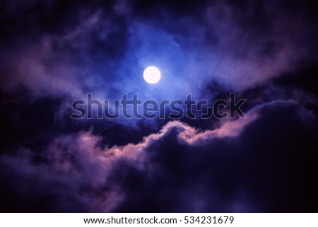 The moon on the dark sky among the clouds, natural abstract background. #534231679