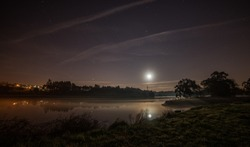 The moon shining in the sky full of stars and reflected in the lake below
