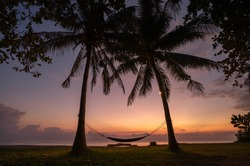 the morning light in shade of purple and orange shine bathe the sky before sunrise with a silhouette of cradle tied with two coconut trees to rest and relax