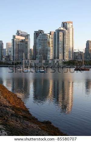 The morning light on the apartment buildings and condominiums of Vancouver's Yaletown neighbourhood reflect in False Creek. British Columbia, Canada.