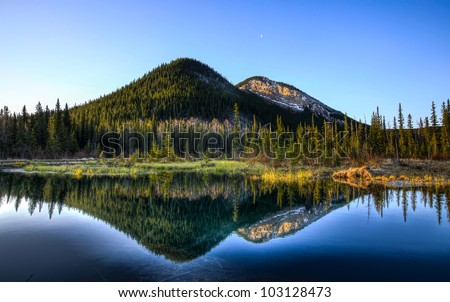 The morning Moon shines above the Elbow Valley in Kananaskis Country, Alberta, Canada.