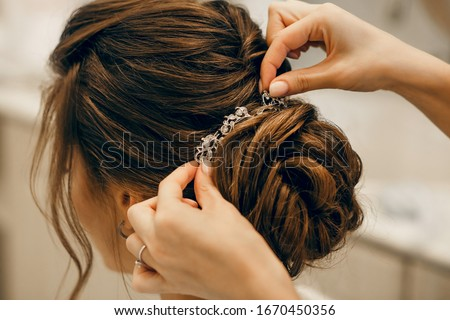 The morning of the bride. Girl makes a stylish hairstyle, a friend helps the bride, a beautiful hair ornament, preparation for a party, close-up hairstyle Foto stock ©