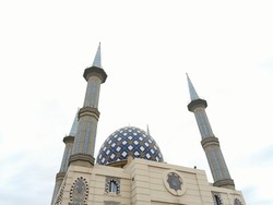 The mosque building which has a dome, minaret and the writing of Allah in front of it is a place of worship for Muslims