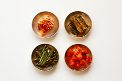The most famous Korean food Kimchi set(napa cabbage, leaf mustard, turnip, leek kimchi ) in high quality brass tableware. Isolated on white background. Top view.