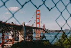 The most famous landmark of San Francisco Golden Gate Bridge through a hole in the fence during a clear day