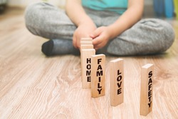 The most important family values presented by the child. The little boy arranges wooden blocks with the words HOME, LOVE, FAMILY. The boy shows what he needs to be a happy child.