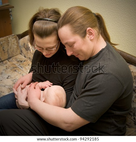 The mother breastfeeding the baby, the father hugging them. Happy Family - stock photo