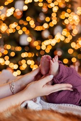 The mother holds foots of the newborn baby in her hands. Birth of children Christmas gift. Parenthood planning. Lovely heels toes are cute. New year background. Innocence. Motherhood