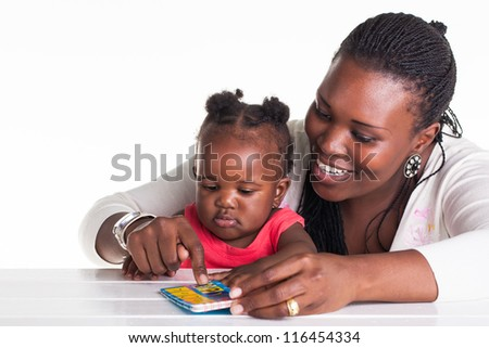 The mother is teaching her daughter some alphabet letters. - stock photo