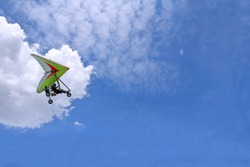 The motorized hang glider flying in the blue sky