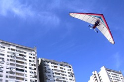 The motorized hang glider flying over residential buildings in the city
