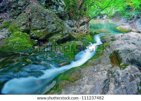 The mountain river flowing down a mountain lake