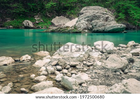 The mountain river Khosta with boulders, stones and pebbles on its sides in springtime. Clear green water of the burly creek in yew-boxwood grove park in Sochi, Adler district, Russia. Stockfoto ©