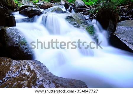 The mountain river precipitously flows, making mini waterfalls