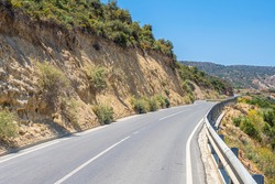The mountain road is empty. The road runs between the rocks. Travel to the Mediterranean coast. Travel by car. A trip to beautiful places on a summer day.