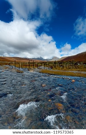 the mountain small river against a glacier and rocks with the dark blue sky and magnificent clouds (Altai)
