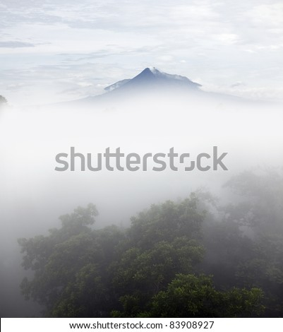 The mountain top of Mount Merapi exposed above a foggy valley on a cool early morning.