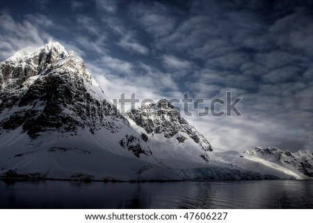 The mountains and clouds with reflection in the water. Antarctica