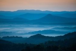 The mountains on the Blue Ridge Parkway welcome the morning with light and mist. Fog is forming in the valley as the sun comes up lighting up the day.