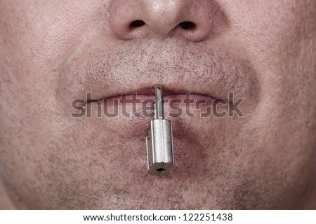 The mouth is closed with a padlock. The symbol of silence and censorship.
