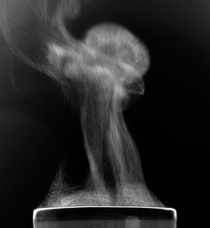 The movement of steam over the cup. Liquid evaporation. Black and white.