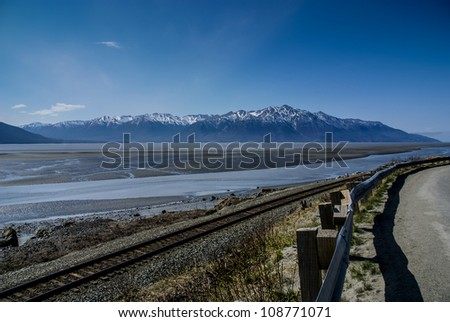 The Mud Flats of the Turnagain Arm Before the Return of the Bore Tide.  From the Seward Highway (1) Near Anchorage, Alaska.  A Beautiful Wilderness Landscape of Rock, Snow, Water and Ice.