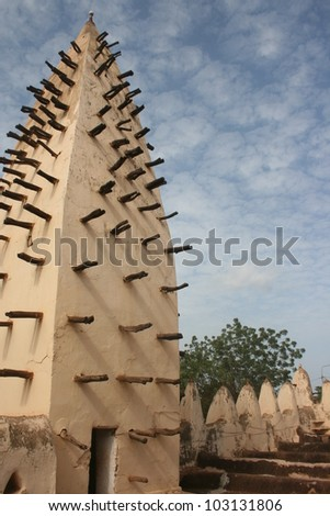 The mud spire of a mosque in  Burkina Faso Africa is studded with wooden beams so people can climb and re plaster the walls after a heavy rain.