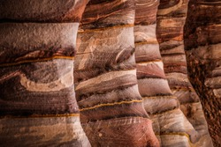 The multi-colored exposed sandstone rock and mineral layers inside the ancient tombs of Petra, Jordan