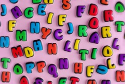 The multi-colored letters of the English alphabet are scattered on a pink background. Learning the alphabet. The concept of education in kindergarten and school. Alphabet for stores, sales, websites