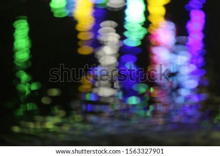 The multi colors of neon light defocused seen through the water in the night time saw many colors in cool color tone. The lights gradually reduce the contrast from top down to the bottom. #1563327901