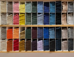 The multicolor socks are arranged in an orderly manner on shelf in a shopping mall