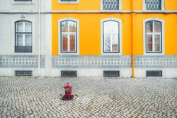 The multicolored facade of an old traditional residential building in Lisbon; view of the colorful frontage of a dwelling house in Portugal with a vivid yellow wall and a red  fire hydrant on pavement