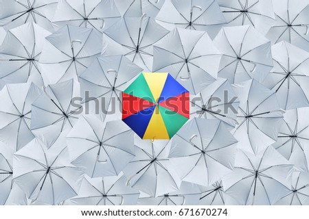 The multicolored umbrella over the gray umbrella, which distinguishes the business model, Being different concepts, Business concept, Top view.