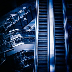 The multiple steps and directions of an escalator in the modern shopping mall , black and white background