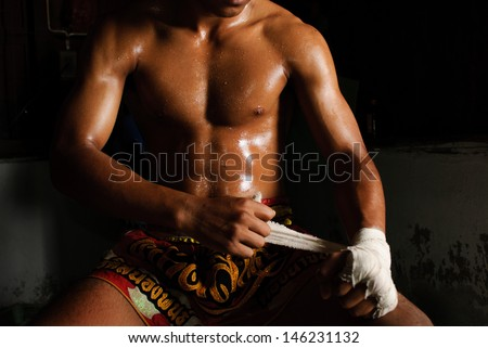 The muscular fighter tying tape around his hand preparing to fight