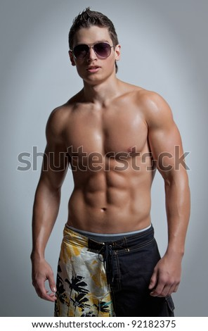 The muscular young naked smiling sexy boy in the beach shorts and sunglasses
