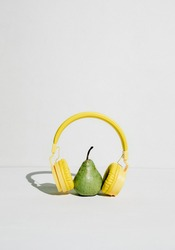 The music player in the shape of an pear with headphones. Fantasy on the theme of music and fruits, podcast for a healthy lifestyle