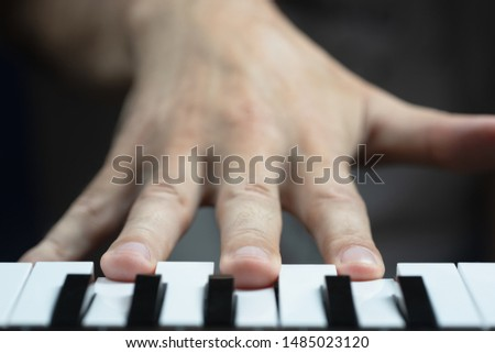The musician presses the keys in D minor chord. Selective focus