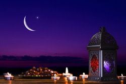 The Muslim feast of the holy month of Ramadan Kareem. Beautiful background with a shining lantern, dates on the tray against the night sky with stars and Crescent moon. Free space for your text