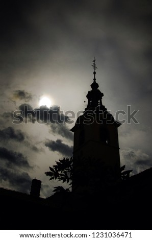 the mystical silhouette of an church bell tower with the dark sky in the background, vertical wallpaper, spooky atmosphere