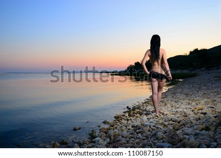 The naked girl at sunset on the sea