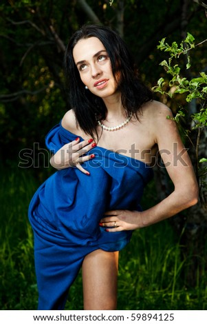 The naked girl is covered with a dark blue plaid in a garden
