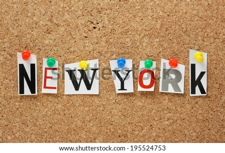 The name New York in cut out magazine letters pinned to a cork notice board