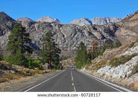 The narrow asphalt road in the picturesque blooming steppe to the distant mountains